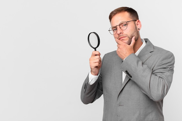Handsome businessman finfing with a magnifying glass
