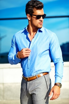 Handsome businessman in formal clothes posing in the street in sunglasses