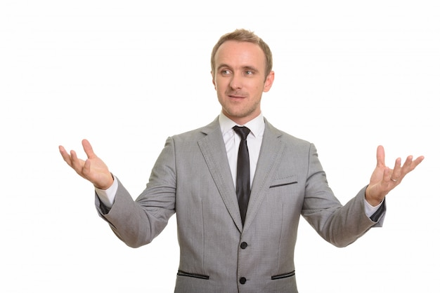 Handsome businessman giving speech isolated against white wall