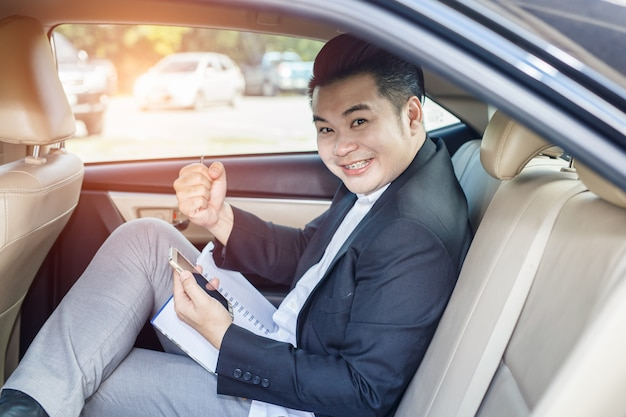 Handsome businessman glad to be successful sitting on backseat of car and touching telephone
