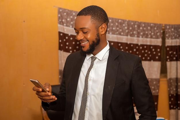 ハンサムなビジネスマンは彼が彼の携帯電話で見たものに興奮しました
