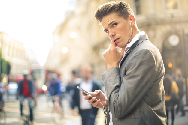 Handsome businessman having a call at the phone while walking in the street