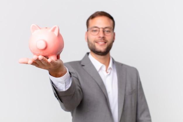 貯金箱を持っているハンサムな実業家。貯蓄の概念