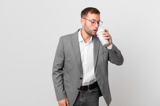 テイクアウトコーヒーを保持しているハンサムなビジネスマン
