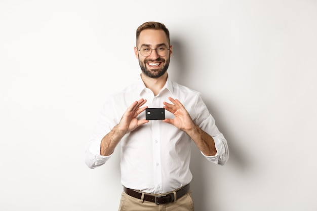 Handsome businessman holding a card, smiling satisfied, standing