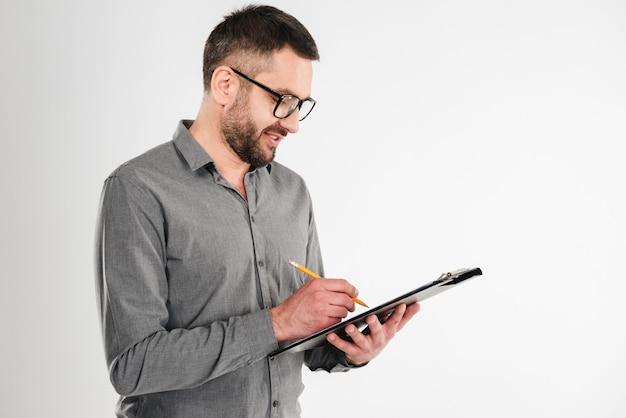 Красивый бизнесмен держа примечания сочинительства доски сзажимом для бумаги.