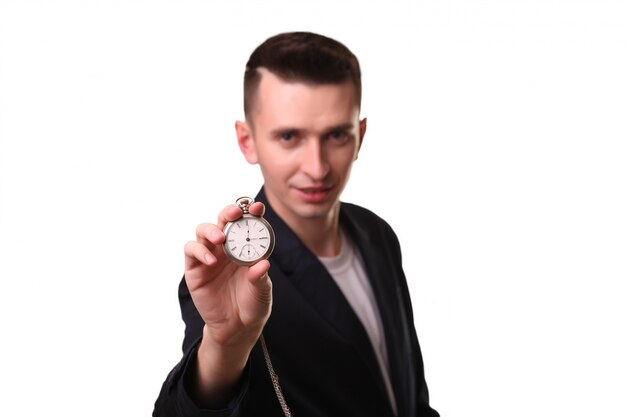 Handsome businessman holding a clock. over white wall