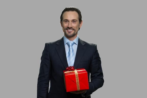ギフトボックスを保持しているハンサムなビジネスマン。灰色の背景にギフトボックスを保持しているビジネススーツの白人男性の笑顔。ホリデーギフトのコンセプト。