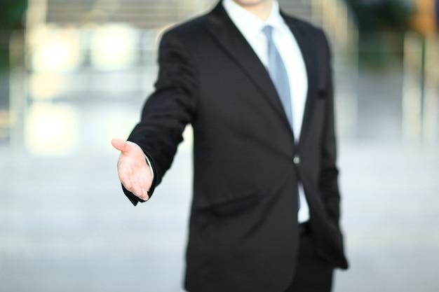 握手のために手を差し伸べるハンサムなビジネスマン。