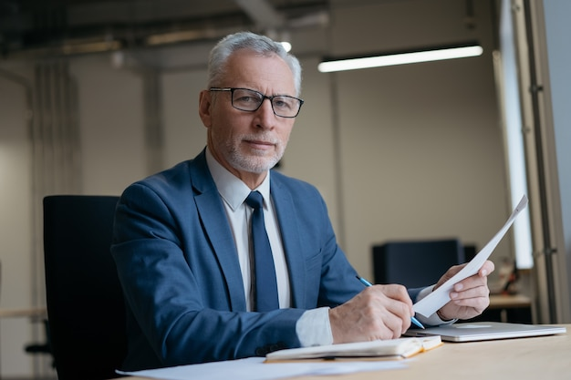 Красивый бизнесмен, держащий бумажные документы, работающие в современном офисе. успешный бизнес
