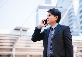 ハンサムなビジネスマンは、携帯電話を使用して、現代の都市の背景に立っている。