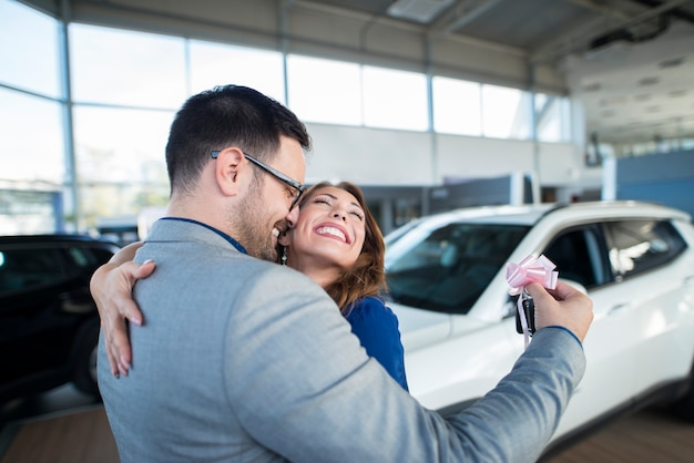 Handsome businessman husband holding keys and surprising his wife with a new car at vehicle dealership showroom