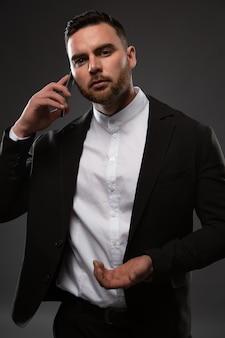 電話で話しているスーツを着たハンサムなビジネスマン。