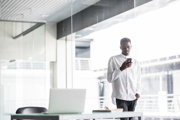 カジュアルな服や眼鏡でハンサムな実業家は、オフィスでの携帯電話での使用