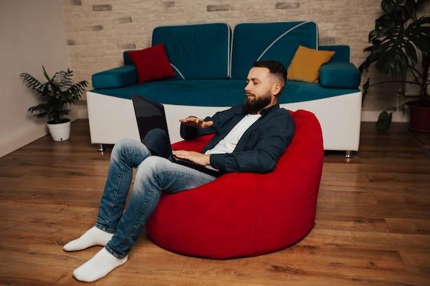Красивый бизнесмен в повседневной одежде использует ноутбук для видеоконференции со своими сотрудниками.