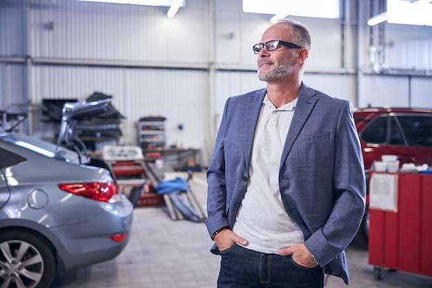 Красивый бизнесмен в очках смотрит в сторону и улыбается, держа руки в карманах