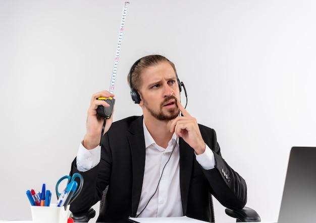 スーツとヘッドフォンでハンサムなビジネスマンは、白い背景の上のオフィスでテーブルに座って困惑して脇を見てメジャーテープを保持しているマイクを持っています