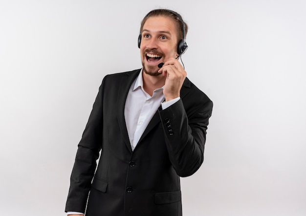白い背景の上に立って幸せそうな顔で笑顔のクライアントを聞いて脇を見てマイクとスーツとヘッドフォンでハンサムなビジネスマン