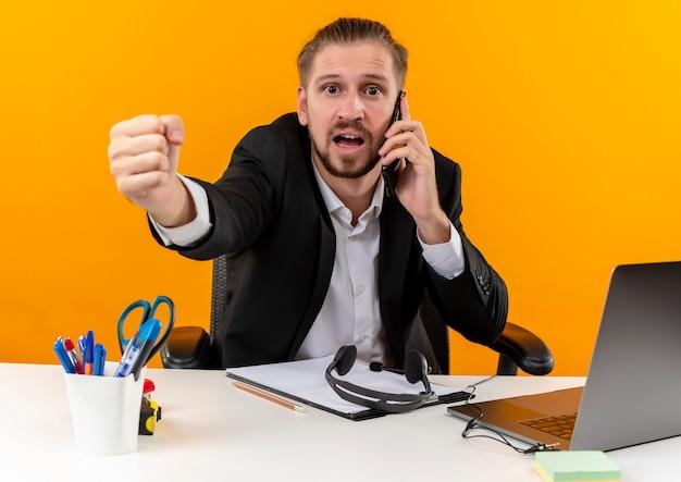 오렌지 배경 위에 offise에서 테이블에 앉아 혼란 찾고 휴대 전화에 얘기하는 노트북에서 작업하는 소송에서 잘 생긴 사업가