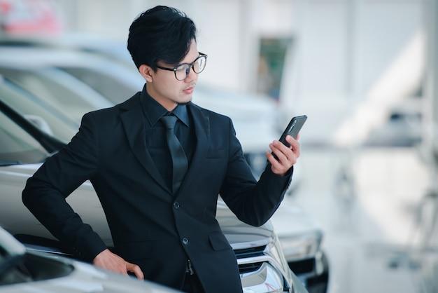 オフィスで電話で話しているスーツと眼鏡のハンサムなビジネスマンは、新しい自動車ショールームの販売が完了したことを祝福します。