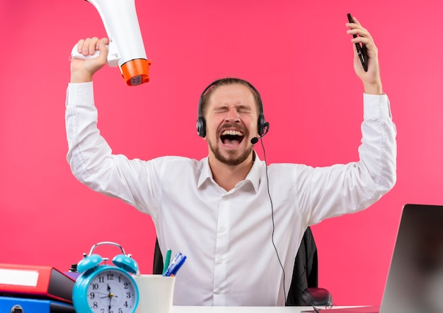 ピンクの背景の上にオフィスでテーブルに座って積極的な表情で叫び、叫んでメガホンを保持しているマイクと白いシャツとヘッドフォンでハンサムなビジネスマン