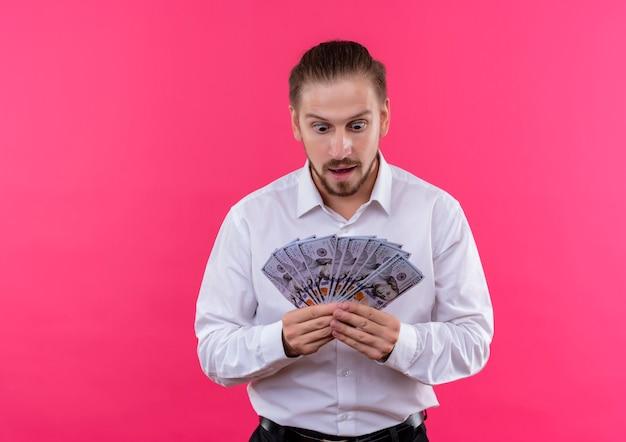 ピンクの背景の上に立って驚いて驚いたように見える現金を保持している白いシャツのハンサムなビジネスマン
