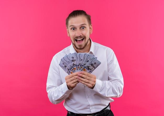 ピンクの背景の上に立って驚いて驚いたカメラを見て現金を保持している白いシャツのハンサムなビジネスマン