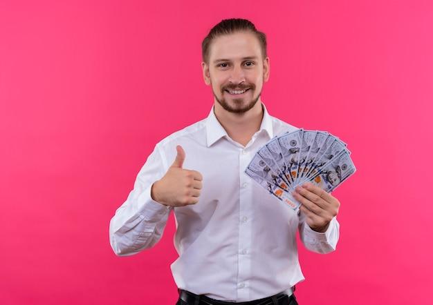 ピンクの背景の上に立って親指を元気に見せて笑顔のカメラを見て現金を保持している白いシャツのハンサムなビジネスマン