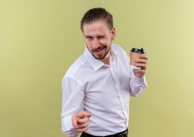 オリーブの背景の上に立って笑顔とウインクカメラを見てコーヒーカップを保持している白いシャツのハンサムなビジネスマン