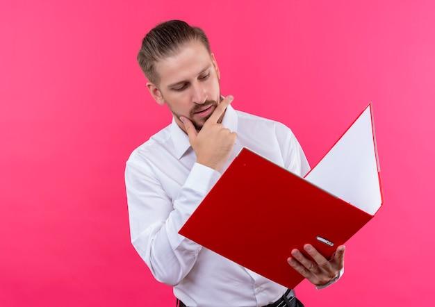 ピンクの背景の上に立っている深刻な顔でそれを見てフォルダーを保持している白いシャツのハンサムなビジネスマン