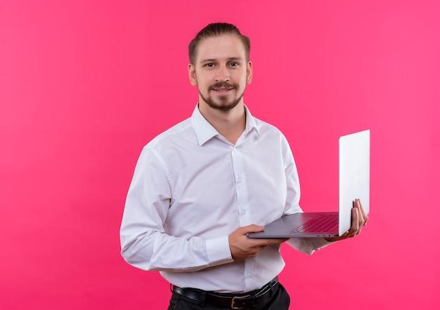 ピンクの背景の上に立っている自信を持って笑顔でカメラを見てラップトップを保持している白いシャツのハンサムなビジネスマン