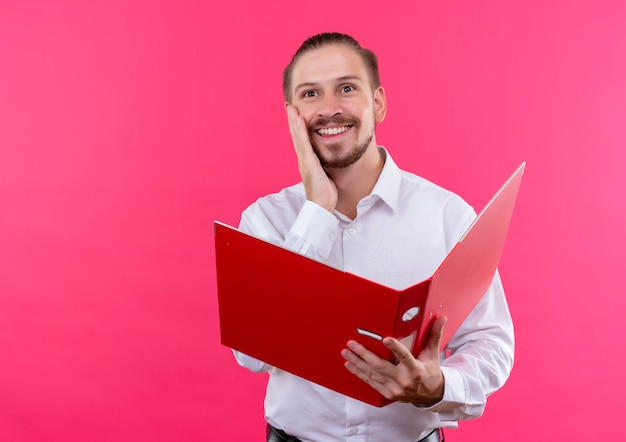 ピンクの背景の上に立っている前向きな感情を感じている顔に笑顔で脇を見て開いているフォルダを保持している白いシャツのハンサムなビジネスマン