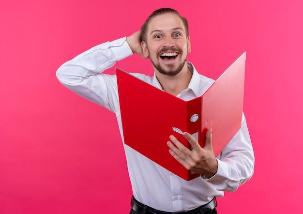 ピンクの背景の上に立って幸せで興奮してカメラを見て開いているフォルダを保持している白いシャツのハンサムなビジネスマン