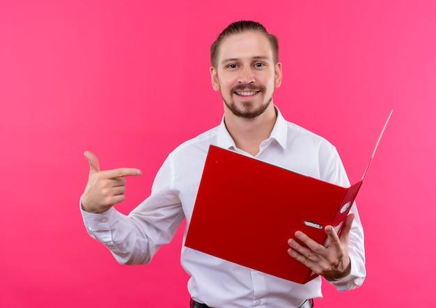 ピンクの背景の上に立って微笑んでそれに指で指しているカメラを見て開いているフォルダを保持している白いシャツのハンサムなビジネスマン