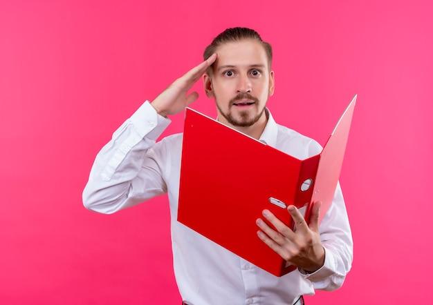 ピンクの背景の上に立って敬礼を驚かせたカメラを見て開いているフォルダを保持している白いシャツのハンサムなビジネスマン