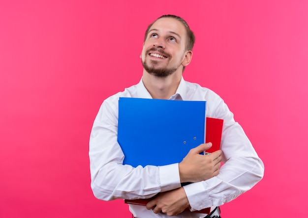 ピンクの背景の上に前向きに立って物思いにふける表情で脇を見て2つのフォルダーを保持している白いシャツのハンサムなビジネス