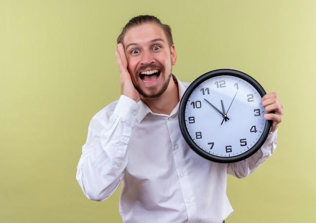 カメラを見て壁時計を保持している白いシャツのハンサムなビジネスマンは、オリーブの背景の上に立って驚いて驚いた