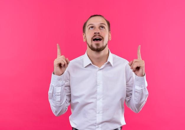분홍색 배경 위에 행복하고 긍정적 인 서 검지 손가락으로 가리키는 찾고 흰 셔츠에 잘 생긴 사업가