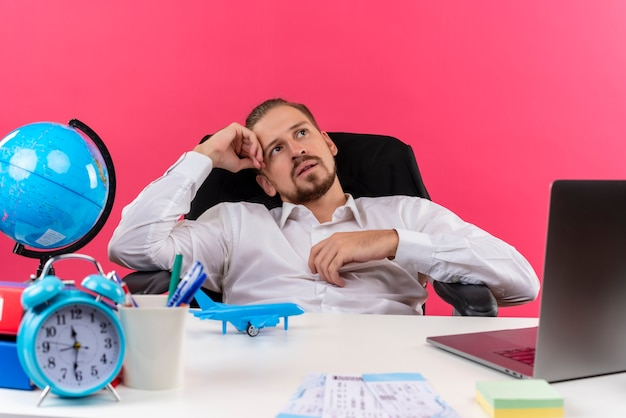 ピンクの背景の上のオフィスでテーブルに座って夢のような表情で見上げる白いシャツのハンサムなビジネスマン