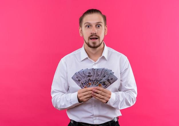 ピンクの背景の上に立って驚いて見える現金を示す白いシャツのハンサムなビジネスマン