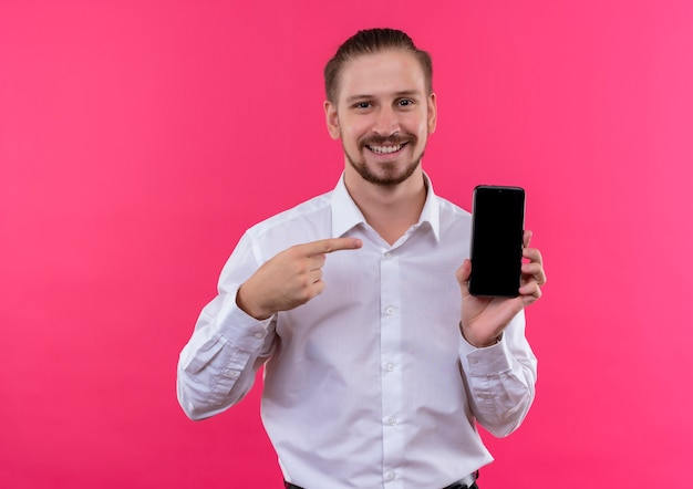 ピンクの背景の上に立っている幸せな顔で笑顔でそれに指で指しているスマートフォンを示す白いシャツのハンサムなビジネスマン