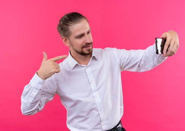 ピンクの背景の上に立って笑顔の彼のスマートフォンを使用してselfieを取る白いシャツのハンサムなビジネスマン