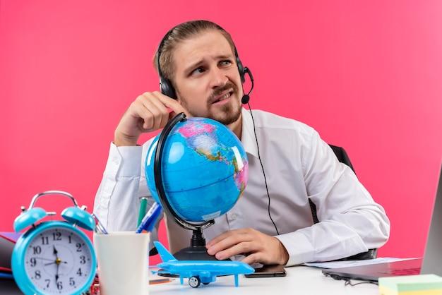 ピンクの背景の上のオフィスでテーブルに座って混乱して脇を見てヘッドフォンが地球に触れている白いシャツのハンサムなビジネスマン