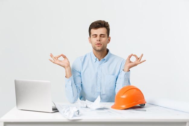 ハンサムなビジネスマンは、伝統的なヨガの蓮華座に座って、オフィスでリラックスしています。