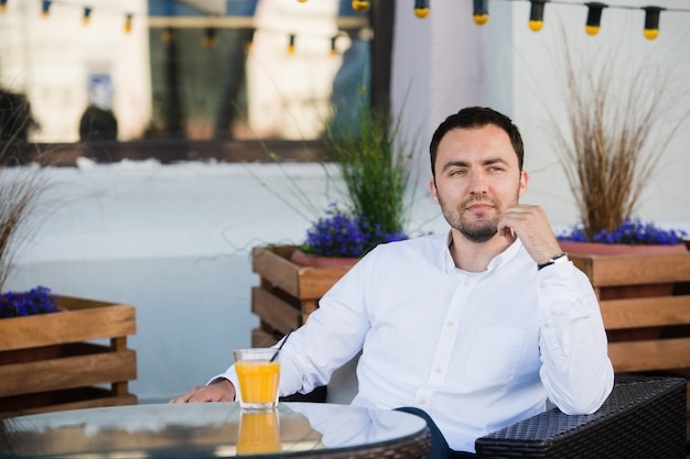 Handsome businessman is waiting for client in cafeteria. he is touching watch and looking to it with anticipation. man is sitting at table outdoors and smiling.