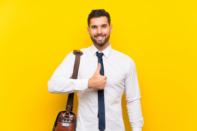 Handsome businessman over isolated yellow wall giving a thumbs up gesture