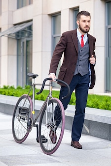 Handsome businessman in a jacket and red tie and his bicycle on city streets.