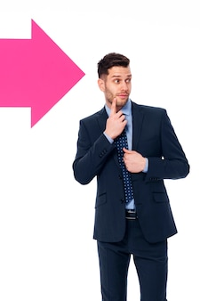 Handsome businessman looking in the direction in which the arrow showing