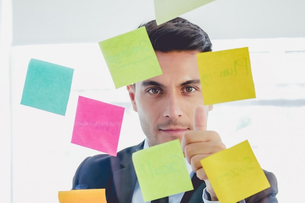 Handsome businessman looking straight sticky notes and thumb up in glasses stands in creat