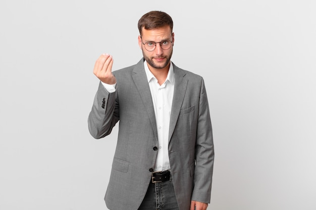 Handsome businessman making capice or money gesture, telling you to pay